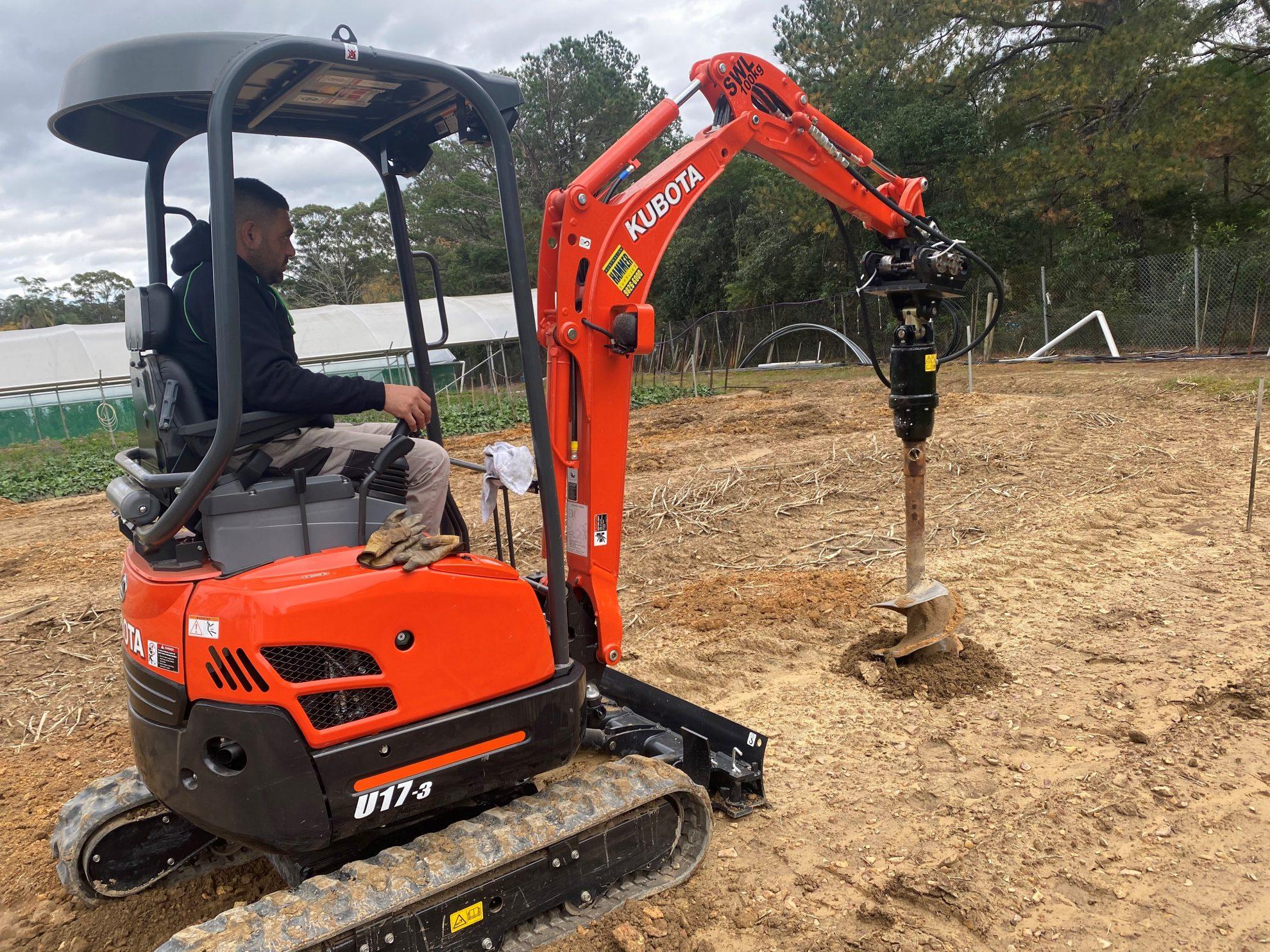 Man drilling a land using a Kubota excavator