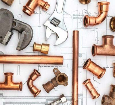 Different types of copper plumbing fittings and wrenches